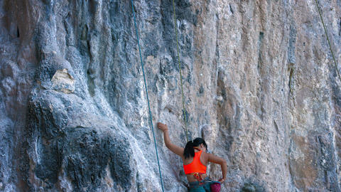 Female rock climber slowly climp up the rock with safety... Stock Video Footage