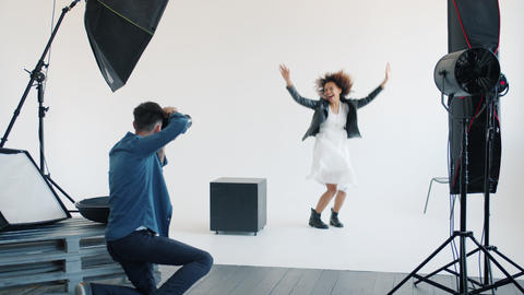 Attractive mixed race lady posing for camera jumping in studio with photographer Live Action