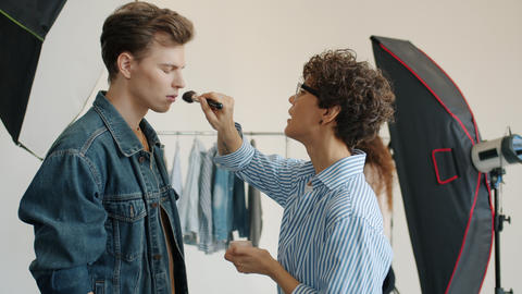 Woman make-up artist busy with male model beautifying guy indoors in studio Live Action
