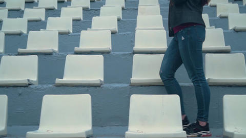 Legs of a girl in jeans and sneakers among the seats of the stadium Live Action