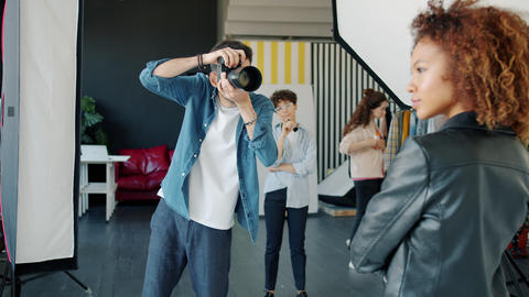 Serious photographer taking pictures of mixed race model in studio talking using Live Action
