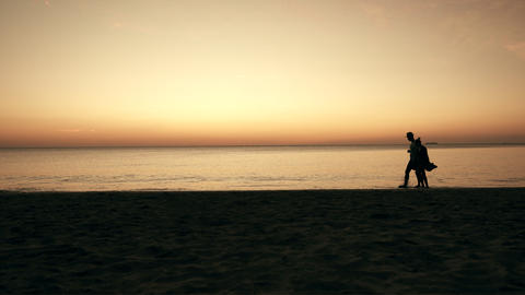 Couple enjoying in sunset on beach, people walking at the beach Live Action