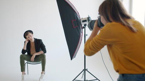 Slow motion of attractive male model posing for photographer in modern studio Live Action