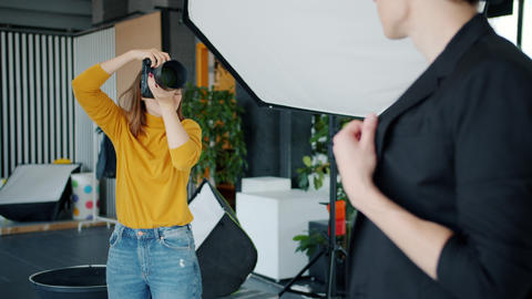 Professional photographer taking pictures of male model using camera in studio Live Action