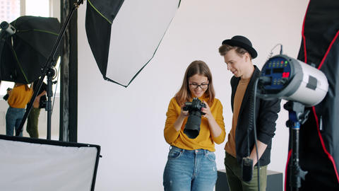 Model and photographer watching photos on camera after photo session in studio Live Action