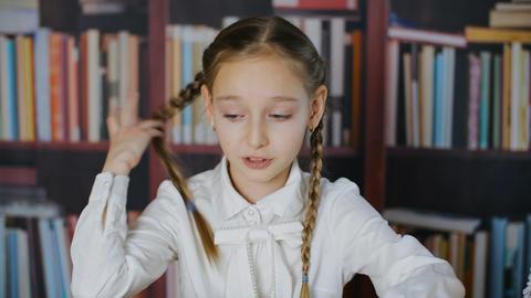 Portrait nervous schoolgirl on bookshelf background in class room. Panic school Live Action