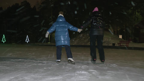 Mom together daughter skating on skates on night ice rink in winter park while Live Action