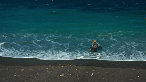 Balinese woman collect sea water on black volcanic sand beach Footage
