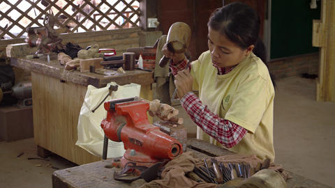 Local woman carves elephant from wood using traditional tools. Video 3840x2160 Footage