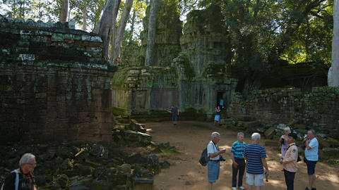 Tourists stroll amongst ruins at Ta Prohm in Angkor. Cambodia Footage