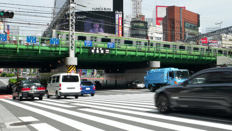 Tokyo - May 2016: Street view with traffic and trains passing by. Shinjuku. 4K r Footage