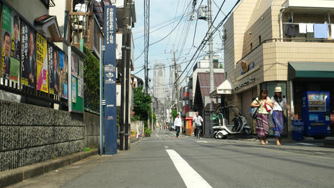 Tokyo - May 2016: Small quiet lane with skyscraper in background and people walk Footage