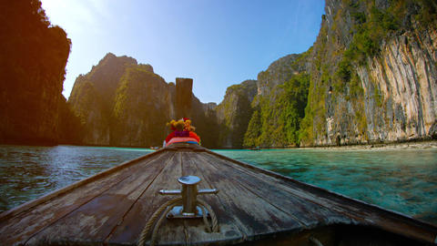 Traditional wooden boat floats between the limestone rocks. Phi Phi. Thailand Footage