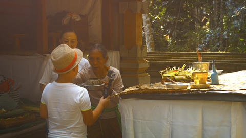 Son with his mother at Tirtha Empul temple. Bali. Indonesia Footage