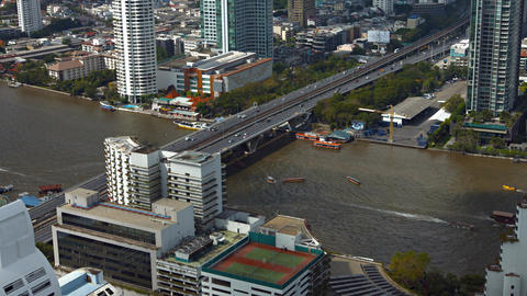 Vehicles cross bridge over Chao Phraya River as boat traffic passes below Footage