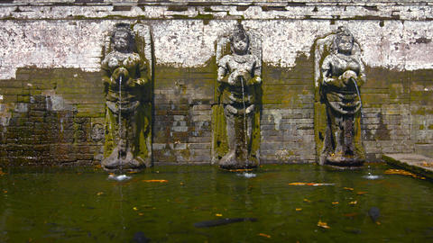 Stone sculptures of women pouring water from jars into pool. In Bali. Indonesia Footage