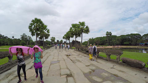 Tourists walking along the entrance road to Angkor Wat Footage