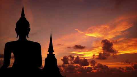Timelapse abstract of silhouetted Buddha image. with drifting clouds Footage