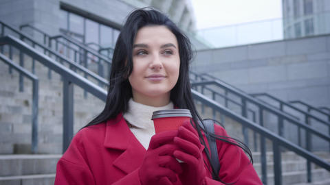 Portrait of young beautiful Caucasian woman with black hair drinking coffee in Live Action