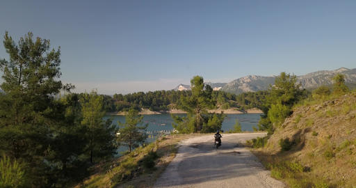 Person is driving a bike on a road near a lake with mountains on the background Live Action