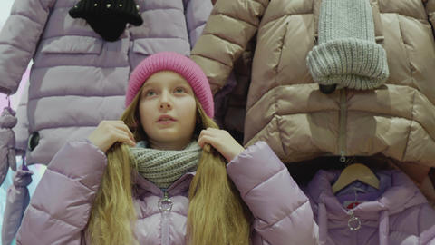 Teenager girl trying new jacket in fashion showroom while shopping. Shopper girl Live Action