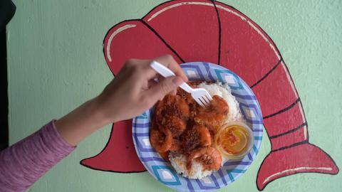 Shrimp truck food from Oahu Hawaii. Woman eating traditional local Hawaiian food Live Action
