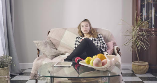 Portrait of teen Caucasian girl sitting on couch and watching TV. Pretty young Live Action