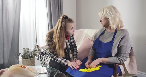Young Caucasian girl in casual clothes calming down senior grandmother. Upset Live Action