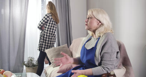 Senior Caucasian woman educating teen girl standing with irritated facial Live Action