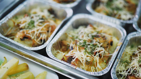 foil containers of delicious meal on canteen counter closeup Live Action