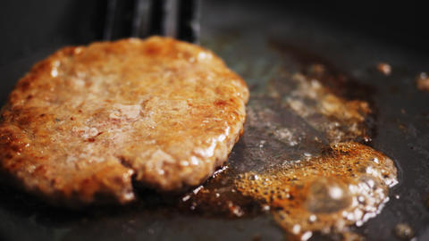 frying fresh cutlet for hamburger on modern pan slow motion Live Action