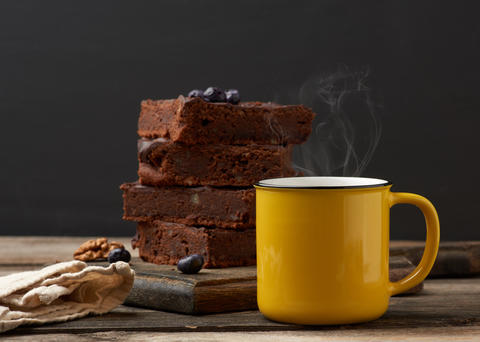 yellow ceramic cup with coffee and a stack of baked brownie piec Fotografía