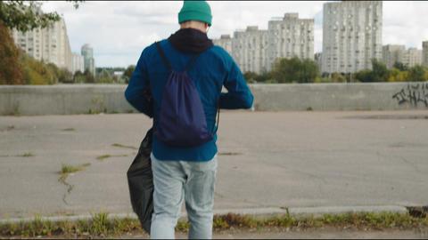 guy volunteer with plastic garbage bag walks along street Live Action