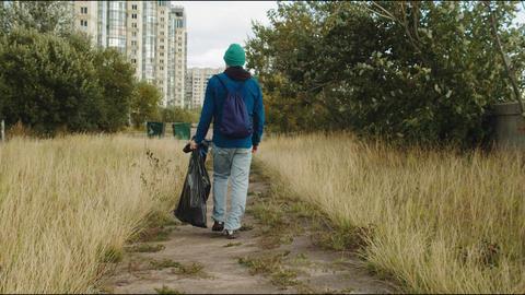 volunteer carries plastic bag with garbage to trash bins Live Action