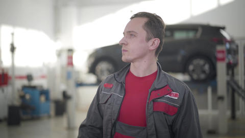 Young male auto mechanic looking around in repair shop and thinking. Portrait of Live Action