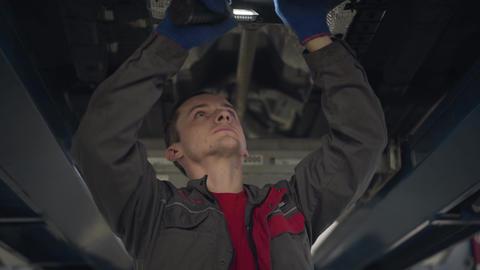Bottom view of professional Caucasian man using flashlight to examine car bottom Live Action