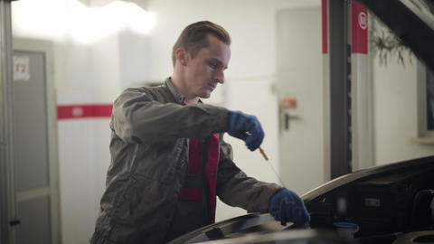 Professional Caucasian auto mechanic checking engine oil. Serious young man Live Action
