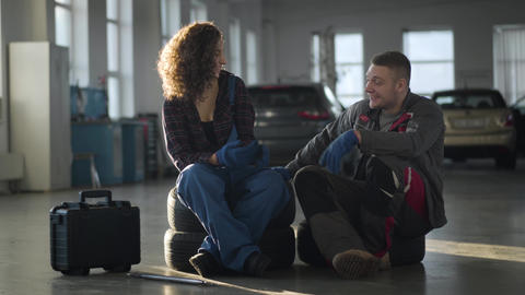 Positive male and female auto mechanics sitting in repair shop, smiling and Live Action