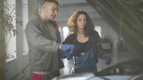 Portrait of professional male auto mechanic teaching female colleague. Caucasian Live Action