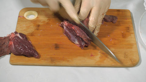Cutting of meat of wild elk. Dark raw meat processing. Cutting on a wooden Live Action
