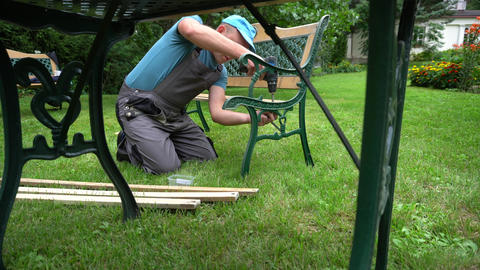 Carpenter guy disassemble retro bench. Outdoor furniture renewal steps Live Action