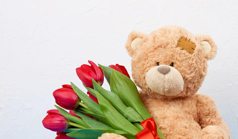 cute brown teddy bear with patches holds in his paw a bouquet of Fotografía