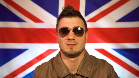 Man in a leather jacket on the background of the flag of Great Britain. A man Live Action