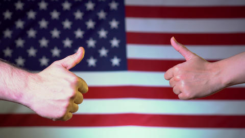 Against the backdrop of the American flag, two hands show thumbs up. US approval Live Action