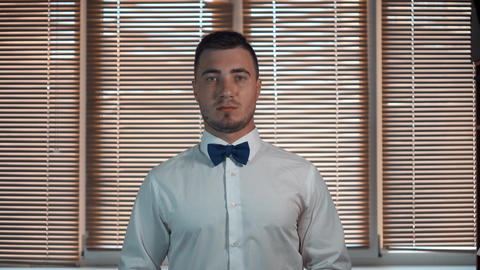 A young man in a white shirt with a bow-tie with a serious face begins to smile Live Action