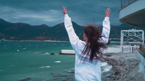A girl stands on the seashore in a storm, her back in the frame, hands to the Live Action
