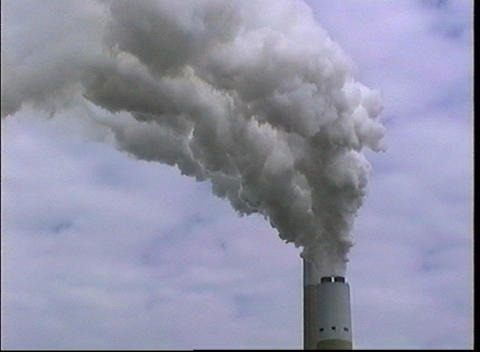 Smoke pours out the top of an industrial smokestack Stock Video Footage