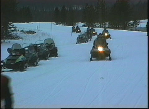 A medium shot of snowmobiles riding down a hillside in... Stock Video Footage