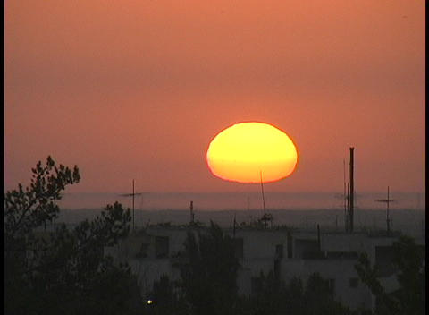 Close-up of the sun at golden-hour behind a foggy rural... Stock Video Footage