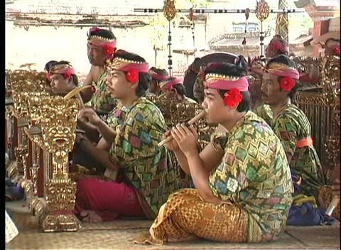 Balinese men playing instruments in an orchestra use a gamelan and flutes Footage
